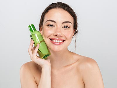 Oil Cleansing Method - Woman with bottle of blended oil