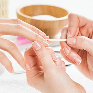 Manicure - Close up of a womans hand being manicured.