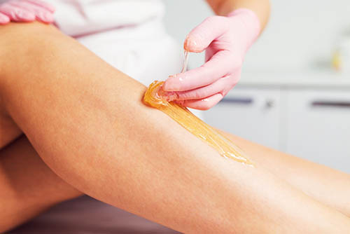 Sugaring hair removal paste being applied to a lower leg